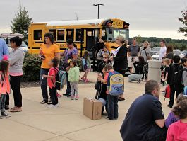 Students and a school bus on the first day of school.
